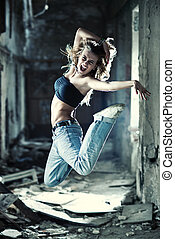 Young woman jumping on industrial background.