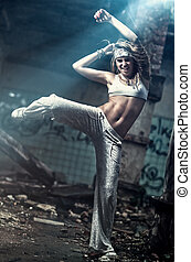 Young woman dancing on industrial background. Angle view.