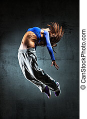 Young woman dancer jumping On wall background
