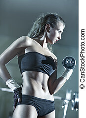 Young woman weight training. Focus on face.