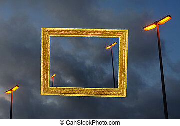 Composition with vintage gold painted frame and orange glowing streetlamps in stormy weather
