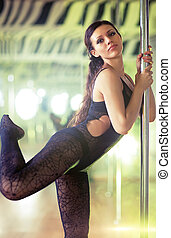 Young pole dance woman. Soft lights effect.