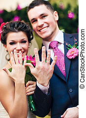 Young wedding couple showing their rings Focus on hands