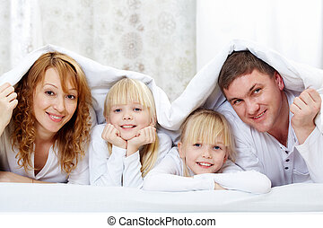 Under blanket - Portrait of cheerful family with twins lying...