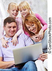 Leisure - Image of happy family together looking at laptop...