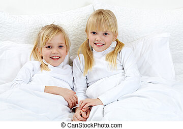 Twins - Portrait of cute twins lying in the bed