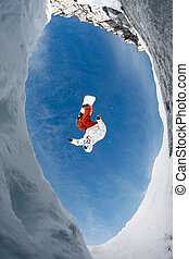In mountains - View from below of snowboarder jumping over...