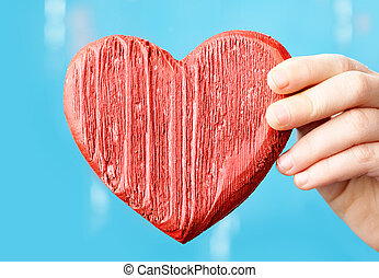 Heart - Close-up of female hand with a red wooden heart