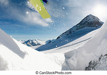 Winter sport - Jumping snowboarder over mountainside at...