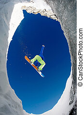 In jump - Below view of extreme snowboarder surrounded by...