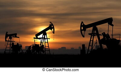 working oil pumps silhouette against sunrise