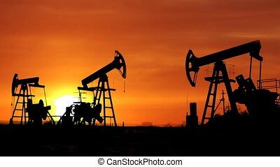 working oil pumps silhouette against timelapse sunrise