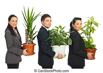 Line of business people holding plants - Line of three...