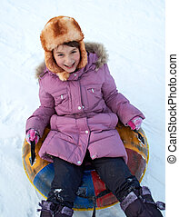 Snow tubing - child riding color covered inner tube down...