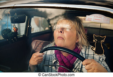 Senior woman in oldtimer car - Concentrated and stressed...