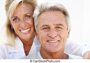 Happy mature couple smiling over white background