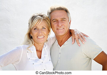 Happy mature couple smiling over white background.