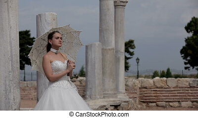 Ancient beauty - Beautiful girl in a wedding dress stands in...