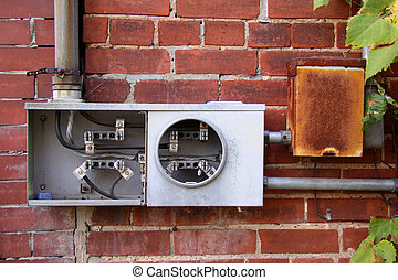 Broken electric meter on a brick wall