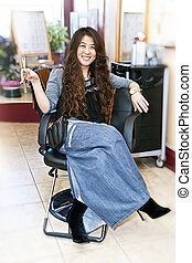 Hair stylist in salon - Hairstylist sitting in a chair in...
