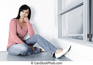 Depressed woman sitting on floor - Sad young black woman...