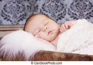 Sleeping infant in vintage crate with damask wallpaper