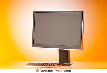 Wide screen computer monitor against colorful background