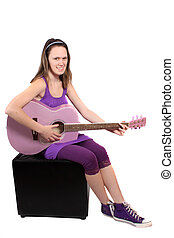 Girl with purple guitar - Teenaged girl plays a chord on...