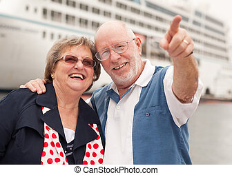 Senior Couple On Shore in Front of Cruise Ship While on...