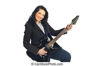 Cheerful guitarist woman in formal wear playing guitar...