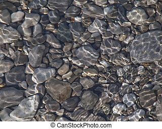 Rocks in water - Smooth stones seen through sunlight in...