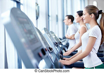Sports people on treadmills - Young attractive girl on the...