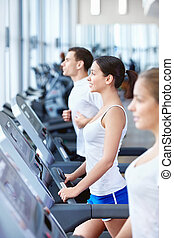 Sports people on treadmills - Attractive young people...