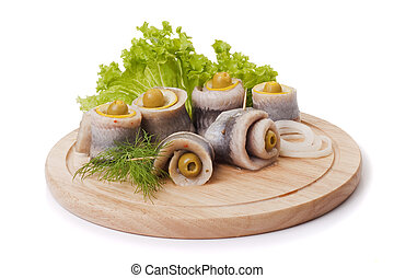 A composition with marinated herring rolls and vegetables on...