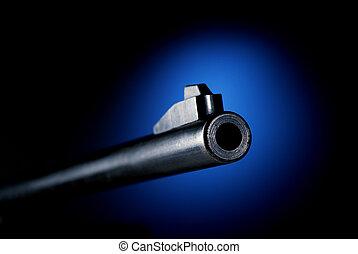 Gun barrel on black background at angle back lit by blue...