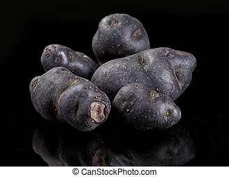 Purple potato vegetable closeup on black with reflection