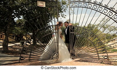 Pair of newlyweds is near the gate