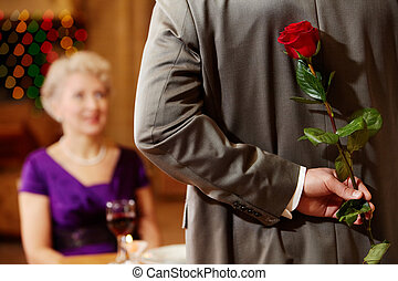 Event - Rear view of man holding red rose in hand on...