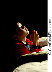 Bedtime prayer - A young boy says his prayers just before...