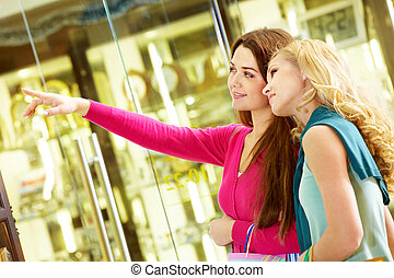 Girls shopping - A woman pointing at something to show her...
