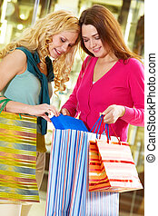 Girlfriends shopping - Two young girls showing purchases to...