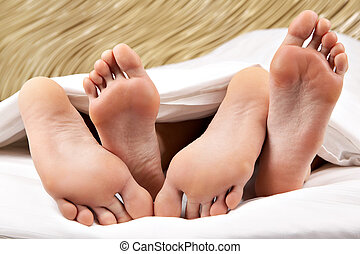 Feet hug - Image of two pairs of bare male and female feet...