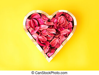 Rose love - Rose petals in heart shape against yellow...