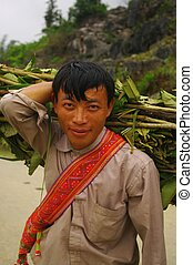 Male Black Hmong flowered with his bundle of wood
