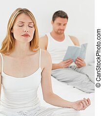 Woman practice yoga while her husband is reading