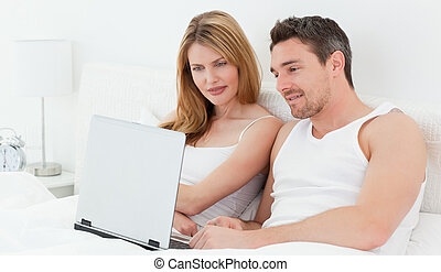 Lovers watching a movie on their laptop
