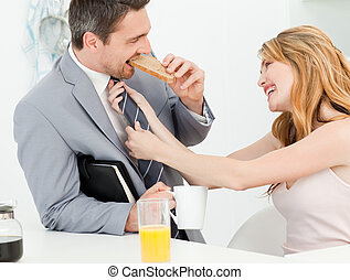 Woman adjusting the tie of her husb