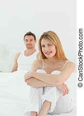 Superb woman looking at the camera with her husband at home