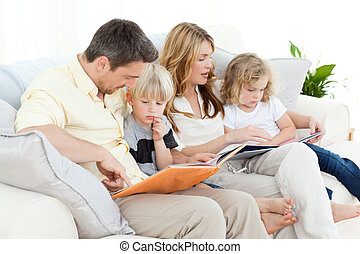 Family reading a book on their sofa at home