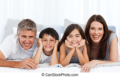 Happy familly looking at the camera on their bed